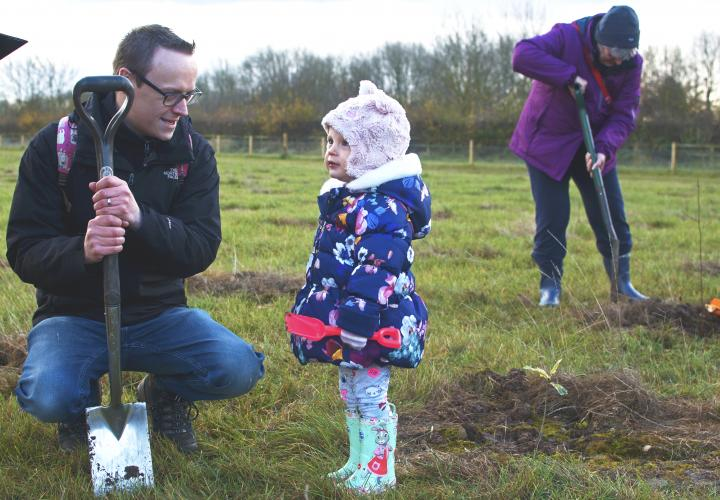 Father and daughter planting a tree.