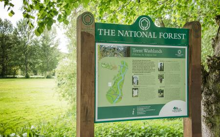 Image of National Forest site information board in a field of green