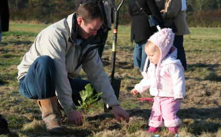 Image of father and daughter planting tree